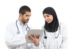 Saudi arab doctors diagnosing looking a medical history Stock Photos