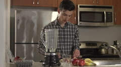 A man puts fruit into a blender in a kitchen. Stock Footage