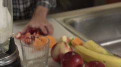 A man puts fruit into a blender, in close-up. Stock Footage