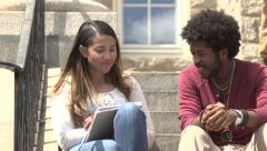An interracial couple chat on school steps. Stock Footage