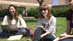 A close-up of racially-diverse students, under tree, studying. Stock Footage