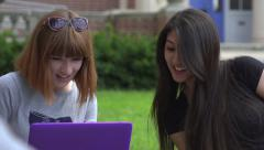 Caucasian and an Asian female students study outside. Arkistovideo