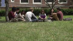 Tilt up to a racially-diverse students studying outside. Stock Footage