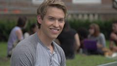 A Caucasian male student, outside, smiles to camera. - stock footage