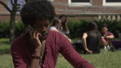 A Black male student argues on cell phone, outside Stock Footage