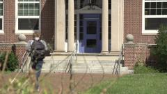 Male Caucasian student runs, late for school. - stock footage