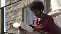 A tilt to a black student using phone on steps. Stock Footage