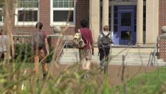 A racially-diverse group of students enter a school. - stock footage