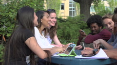 A racially-diverse group of students chat at a table Stock Footage