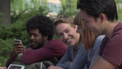 A close-up of racially-diverse students chatting at table Stock Footage
