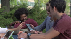 Close-up of racially-diverse students laughing over a digital tablet Arkistovideo
