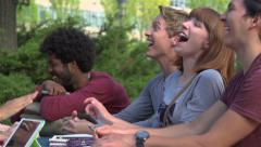 Racially-diverse students laugh at a table in slow motion. Stock Footage