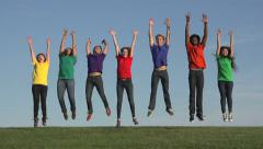 Racially-diverse students jump in celebration - stock footage