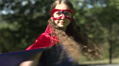 A superhero girl triumphantly poses for camera Stock Footage