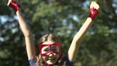 A superhero girl jumps for joy with her arms aloft - stock footage
