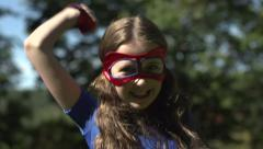 A superhero girls runs to camera a expresses victory Stock Footage