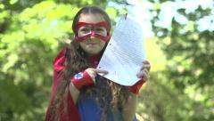 A superhero girl proudly shows off her A+ homework grade Stock Footage