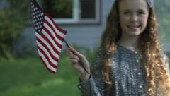 A tween girl smiles at camera in front of her house waving a US flag Stock Footage