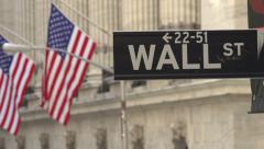 Pan across flags to street sign for Wall Street Stock Footage
