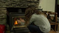 A girl warms her hands in front of a fire Stock Footage