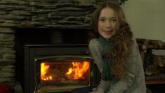 A girl warms her hands in front of a fire, before smiling to camera Stock Footage
