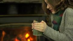 A girl warms herself with a hot drink in front of a fire Stock Footage
