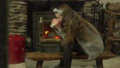 A girl warms herself with a hot drink in front of a fire. It is snowing outside. Stock Footage