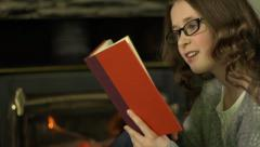 A tween girl sits in front of a fire and reads a book with reading glasses. Stock Footage