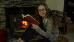 A girl sits in front of a fire and reads a book before smiling to camera Stock Footage