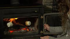 A girl warms marshmallows on a fire Stock Footage