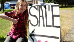 Young girl runs up to yard sale sign. Gives thumbs up. Stock Footage