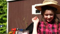 A young girl picks up a straw hat at a yard sale and tries it on. Stock Footage