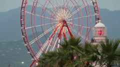 Lighthouse and Ferris wheel and Palms Stock Footage