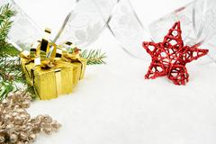 Decoration of gold christmas gifts, silver ribbon on snow with red star, chri Stock Photos
