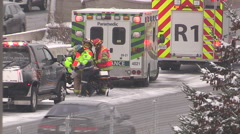 Car accident scene snow storm blizzard highway police ambulance fire trucks Stock Footage