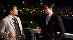 Two men in suits are drinking and talking while on the roof at night. Another Stock Footage