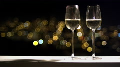 Close up of two champagne flutes with the city lights of San Francisco at night Stock Footage