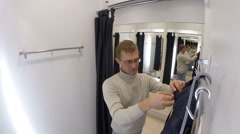 Man trying on a jacket at the store on  OSTIN Stock Footage