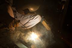Arc welder with welding sparks - stock photo