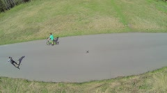 Young bicyclist rides by road with man on roller ski at spring Stock Footage
