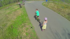 Two kids ride on rollerskates and bicycle by crossroad Stock Footage