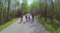 People parents and children ride on rollerblades and bicycle Stock Footage