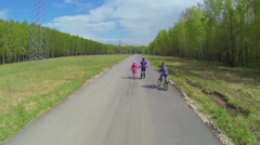Mother with children ride on rollerblades and bike by road Stock Footage
