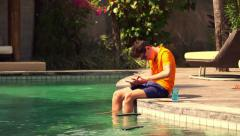 Teenager playing with game on tablet while sitting of swimming pool  HD Stock Footage