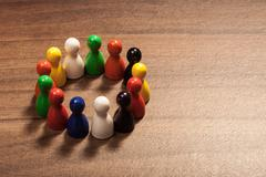 Circle of diversity, figurines on wood table Stock Photos