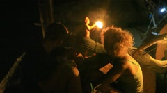 Young man and woman sitting in night bar, drinking a cocktail, watch fire show Stock Footage