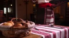 Ukrainian restaurant waiter puts on the table dishes - vareniki and borsch Stock Footage
