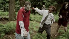 Zombies walking through forest close up Stock Footage