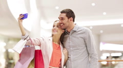 Happy couple with smartphone taking selfie in mall Stock Footage