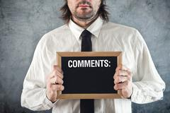 Businessman holding blackboard with comments - stock photo